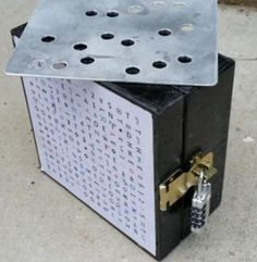 Geocache by Roombacats called Grid and Template on both sides of the box  Use the metal template to decode the 4 letters of the lock combination to access the log.