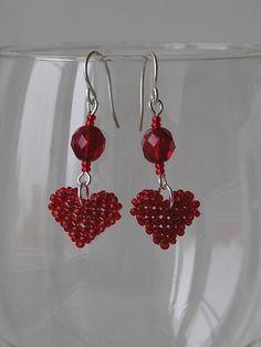 Náušnice - červená srdíčka Červená srdíčka. Srdíčko je navlečené na vlasci. To je připevněno k náušnicovému háčku ketlovací jehlou. Bižuterní kov je stříbrné barvy, korálky v odstínech červené.