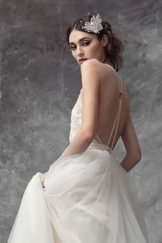 High neck halter gown with ropes of pearls on open back. French lace hand embroidered with rose seed beads and Swarovski crystals. Soft Italian tulle skirt.