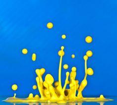 Yellow Paint Splashing Against Blue Background