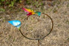 Handmade Copper Hummingbird Hoop with Blue Calla Lily. A unique piece for any garden! This is a handmade hummingbird hoop, with a blue calla lily. To save on shipping cost, the stick does not come with this. It can be purchased at any hardware store.
