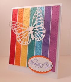 handmade card ... Butterfly over a Rainbow by DCinkit  ...  strips of cardstock in rainbow order with different embossing folder textures ... bright and beautiful!! ... Stampin' Up!