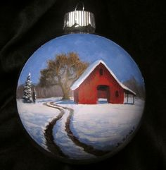 Hand painted Christmas ornament of a red barn in the snow by artist, Jeremy Sams.