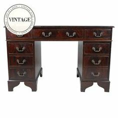"""Circa 1920s mahogany wood writing desk with leather inlay. Wear appropriate with age.   Product: Writing deskConstruction Material: Mahogany and leatherColor: Brown, green and gold  Dimensions: 30.5"""" H x 48"""" W x 24"""" D   Note: Due to the vintage nature of this product, some wear and tear is to be expected. Products may show signs of brand marks, scrapes or other blemishes.Cleaning and Care: Wipe with damp cloth"""