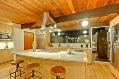 Check out the new countertops in this 1972 #Eichler kitchen we remodeled in Palo Alto: pale green Taj Mahal countertops cut from large blocks so there are no seams, Kraus stainless steel sinks with Moen hardware, custom cabinetry with pull-out drawers for pots and pans, custom-made range hood by Abbaka... #remodel #kitchen