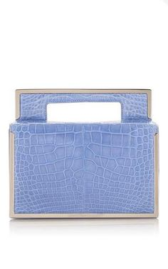 This clutch bag by **Salvatore Ferragamo** is rendered in luxurious celeste blue crocodile and features a delicate metallic edging, a structural top handle and compartmentalized interior.