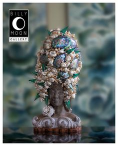 Head Sculpture. Terracotta.  Multi-layered paint finish.  Assorted shell head piece.  Wood base. A1355