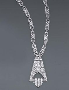 Christie's  IMPORTANT SAUTOIR ART DECO ONYX ET DIAMANTS  Constitué de vingt maillons oblongs sertis de diamants retenant un pendentif triangulaire ajouré de motifs à enroulements pavés de diamants ronds taille brillant, la base soulignée d'une rangée d'onyx calibrés d'où jaillit une cascade de diamants carrés, monture en or et platine, années 1930, 63.0 cm.