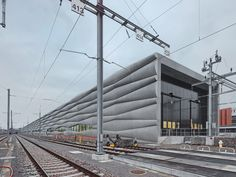 EM2N clad railway service facility with billowing cement facade