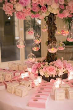 A pink flower arrangement featured suspended glass orbs filled with petals. Photography: Marianne Lozano Photography.