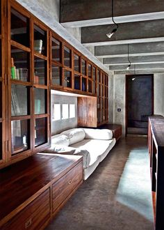 A modern library with wall of wood-lined bookshelves, polished concrete floors, exposed concrete beam ceilings, simple hanging light fixtures, square punched-opening windows, and an upholstered white reading nook.