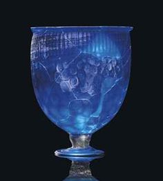 A ROMAN COBALT BLUE GLASS CHALICE   CIRCA 4TH CENTURY A.D.   The deep body mould-made with vertical fluting above a honeycomb pattern, with slightly flaring rim, on a disc foot with knobbed stem  7 1/8 in. (18.1 cm.) high