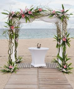 Beach wedding alter with drapes, palms and flowers.... notice the drapes are tied down for wind.