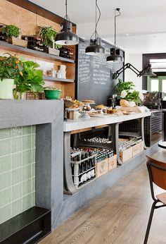 Greys, black fixtures,concrete, wood - chalkboard, plants + polished plywood behind shelves