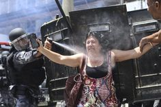 A Brazilan policeman sprays tear gas at a demonstrator