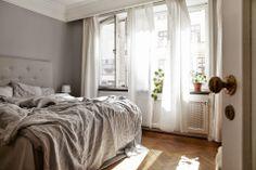 Harmaasta ei saa kylliksi, kun sitä on käytetty noin kauniisti. Valkoinen, iso kattolista tekee tästä huoneesta napakympin.