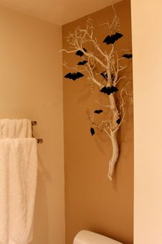 Add a little spooky atmosphere to your home with white branches and glittery bats! Try mounting on your wall with Command(TM) Picture Hanging Strips! #halloweenhomedecor