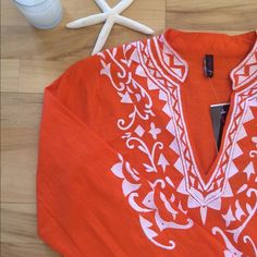 La Moda Clothing sun cover Brand new! La Moda Clothing resort wear. Bright orange tunic cover-up with white embroidery. 100% cotton, hand wash. Size small. Does have a small pull on the lower front- very hard to see. Priced accordingly. La Moda Clothing Swim Coverups