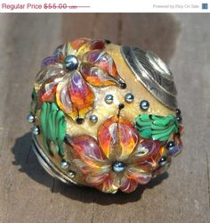 "25% OFF Capped and cored handmade lampwork floral focal bead pendant, ""Shine"". $41.25, via Etsy."