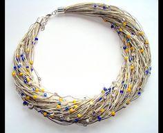 Naszyjnik wykonany z lnianego sznurka w kolorze ecru i w kolorze naturalnego lnu, ozdobiony koralikami toho w kolorach żółty,szafirowy,niebieski,biały-mleczny,przezroczysty z dodatkiem...
