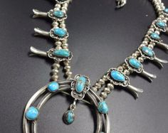 SQUASH BLOSSOM NECKLACE    DESCRIPTION: This impressive necklace is crafted from heavy gauge sterling silver, with 17 perfect specimens of clear blue turquoise set in the sterling sconces. This necklace will be a valuable addition to your collection of fine vintage Native American jewelry.    MEASUREMENTS: Necklace measures 26  Naja measures 2 11/16 x 2 3/4    Handmade bench beads are securely strung on silver wire    WEIGHT: 207.2 grams  SIGNED: G.L., for George Lasiloo (Zuni)    S...