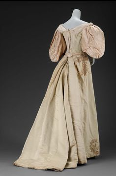 Woman's evening dress about 1895 Light green silk faille dress in two parts. Bodice has large puffed white satin sleeves and is trimmed at center front with pearls and cream chiffon at neckline. Trained skirts has split front edged with cream satin and imitation pearls in floral pattern.