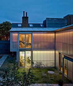The courtyard facade of Jonathan Tuckey's Dulwich Yard House in London is made of a series of translucent polycarbonate panels, the same type used at Herzog & De Meuron's Trinity Laban Centre in nearby Deptford