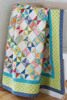 Scrappy fat quarter friendly bed style quilt pattern design by Tailormade Designs that uses the hourglass quilt block.