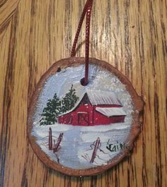 My husband cut this wood slice for me from a piece of oak. I hand painted an old red barn in acrylic and sealed it with a sealer. It has a red twine