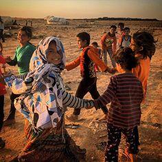 Syrian refugee children hold hands and sing while playing at an informal tented settlement in Jordan. Photo by @mmuheisen #everydayrefugees #muhammedmuheisen