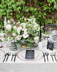 A Super-Stylish and Beautifully Personal California Wedding | Martha Stewart Weddings – At Red Tavern, laser-cut table numbers, menu cards printed in white foil, and taper candles—all in black—stood out against gray velvet linens and verdant centerpieces. Marbled-gray glass vases held begonia leaves and ferns, black scabiosa, ranunculus, dogwood, and black and green hellebores, among others. Alongside, of course, were stacks of river rocks.