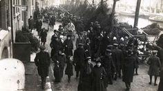 Kerstbomenmarkt op het Singel in Amsterdam. Dennebomen staan aan de waterkant en de mensen lopen in grote getalen over het Singel.  1917