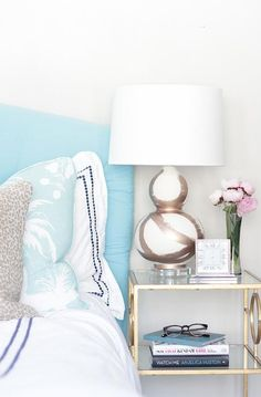 Contemporary bedroom features a turquoise headboard on bed dressed in white and navy hotel duvet and white and blue pearl beaded shams, Pottery Barn Pearl Embroidered Shams in Twilight Blue beside a brass and glass bedside table topped with a Jana Bek Brush Stroke Lamp Rose Gold.