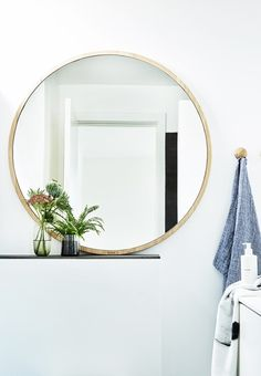 Simple round mirror with a wooden frame in the bathroom.