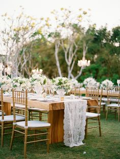 Romantic reception tablescape with white flower centrepieces, a lace table runner and Tiffany chairs. // Ethereal White Wedding at Alila Villas Uluwatu: Francis and Fe #white #gold #wedding