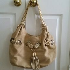 REDUCED! MICHAEL Michael Kors Braided Grommet Tote This chic, slouchy, cinched tote features soft straw with braided, metallic gold leather woven through gold grommets around the bag, 2 braided leather straps, tassels, a hanging logo charm, and magnetic snap tab closure. The interior is MK signature lined fabric, and has a zip pocket, 2 slip pockets, and a leather key clip. Aside from some wear where the metallic finish has worn off a little (mainly straps), and a couple of small marks here…