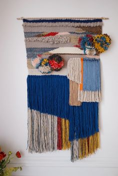 Wall weaving made of silk, natural wool from South Africa, cotton, shiny wool and pompoms. On a wooden stick.44 cm x 85 cm (including the fringes).