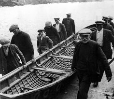 Men from the Blasket Islands, Co. Kerry, carrying a naomhóg, long long ago