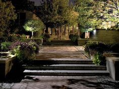 Landscape Lighting Ideas: Another approach to path lighting is to forego it altogether. In this scene designed by Chicago-area lighting firm, uplit trees and downlighting from the house cast ample light on the walkway.You don't have to light every inch of your landscape; there's a place for path lights, but we use them sparingly.