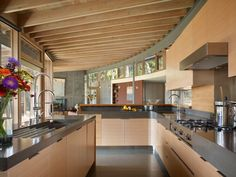 Moderne Küche mit Beton-Arbeitsplatte und Holz-Fronten
