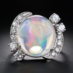 A high-cabochon Mexican opal, weighing 13.40 carats, looks as though it came from another planet! Luminous swirls of kaleidoscopic colors float inside a veritable crystal ball - a holograph on your finger! The magic opal is embraced on each side by sparkling mirror-image flares of bright-white, full-cut diamonds set in platinum. A one-of-a-kind gemological wonder.