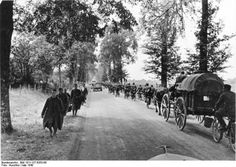 German troops continue to march forward into Belgium while disarmed Prisoners of War are sent to the rear