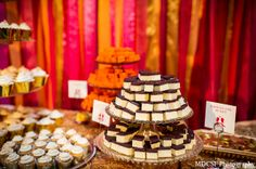 Fusion #Dessert Table | An Indian bride and groom celebrate their wedding reception after their traditional Sikh ceremony. The bride dons a colorful halter lengha and the decor has a gold and pink color palette.
