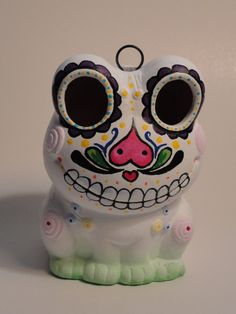 This is a one of a kind piece! This adorable ceramic frog has been hand painted with a sugar skull theme that includes flowery eyes,a great flow of swirls and lines, skull like teeth, and colorful dots added to just the right places.