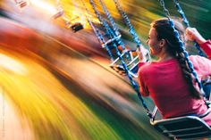 Young woman enjoying swing carousel in the evening. Blurred motion.