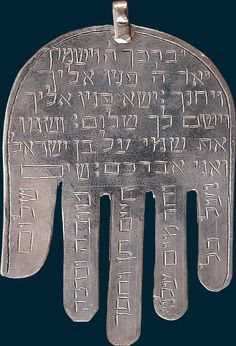 """Cette amulette en argent gravé, en forme de main aux cinq doigts parallèles, d'où l'appellation de Hamsa, qui en arabe signifie """"cinq"""", est recouverte d'inscriptions en hébreu reprenant les versets de la bénédiction sacerdotale contenue dans le livre des Nombres (VI, 24-26) : """"Que l'Éternel te bénisse et te garde, qu'il fasse luire sa face vers toi et te soit miséricordieux, que l'Éternel tourne sa face vers toi et qu'il te donne la paix."""""""