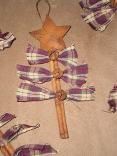 Cinnamon stick Christmas trees: take a cinnamon stick that was about six inches long and cut three graduated sizes of homespun strips. Pleat each strip like an accordion and secure with a bit of brown floral wire. Then hot glue these onto the cinnamon stick. Cover the wire with a rusty jingle bell. Hot glue a rusty star to the top. Voila, a perfectly prim Christmas tree ornie! by bianca