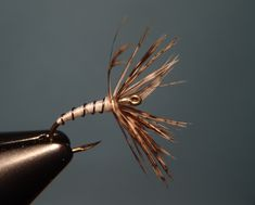 Hook:  TMC 2499SPBL #12  Thread:  White 6/0  Head:  Pearlescent flashabou over a thread foundation  Hackle:  Brown partridge  Body:  White thread  Rib:  Small black wire