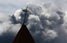 A cross is seen atop a church steeple as ash from Mount Sinabung spews in the background, as seen from Kebayaken village in Karo district, I...