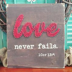 """Love never fails string art is approx. 12"""" x 13"""" Made from reclaimed wood, nails, chalk paint and embroidery thread."""